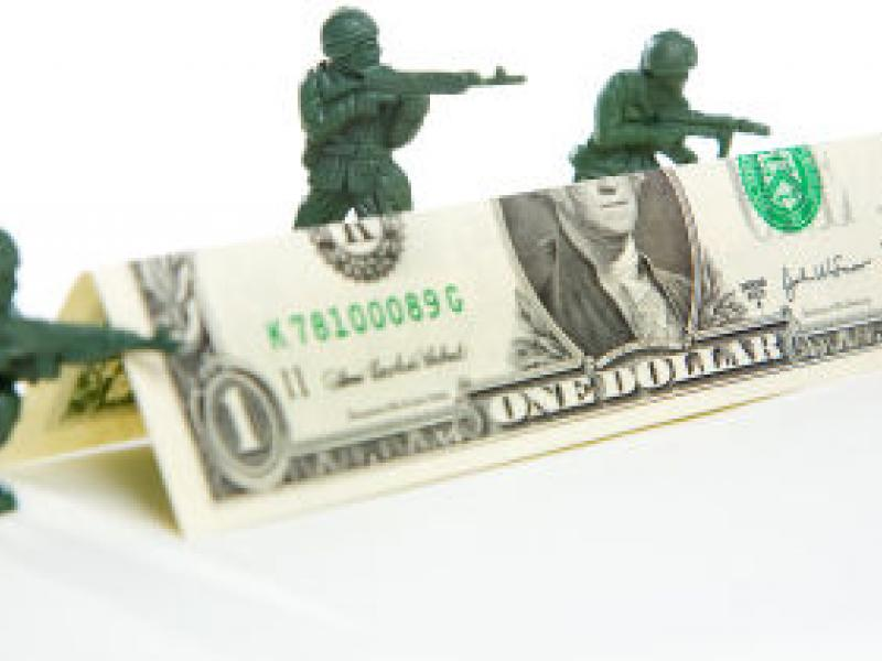 Toy soldiers hiding behind dollar bill